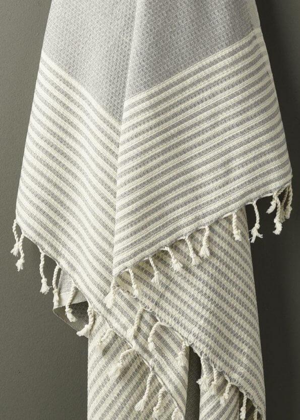 Nært produktbillede af gråt strandhåndklæde med striber