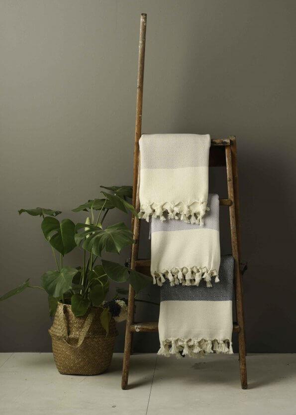 Miljøbillede af strandhåndklæder i sort, grå og beige med diamntmønster