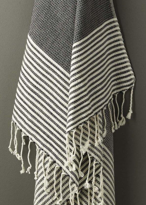 Nært produktbillede af sort strandhåndklæde med striber