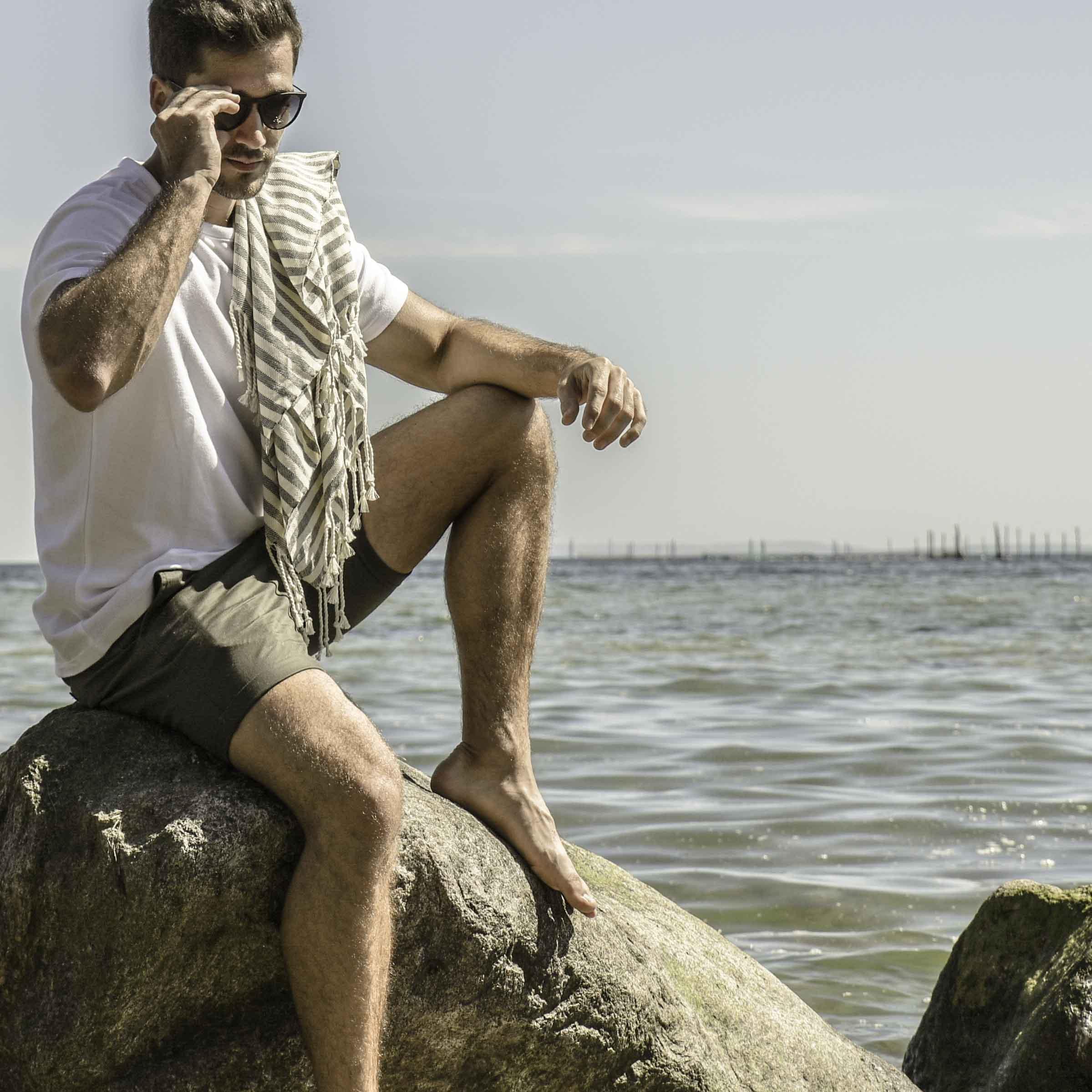 Mand med sol i ansigtet på på strand med strandhåndklæde over skulderen