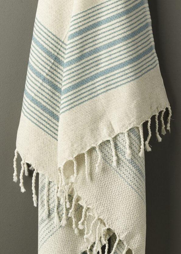 Nært produktbillede af strandhåndklæde i aqua med striber