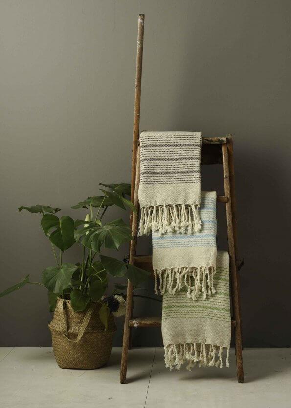Miljøbillede af strandhåndklæde i aqua, brun og grøn med striber
