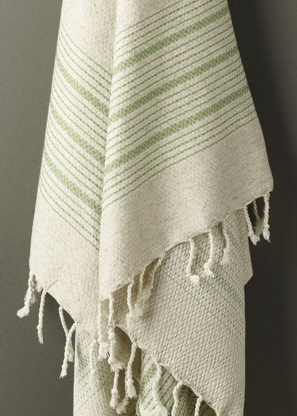 Nært produktbillede af strandhåndklæde i grøn med striber