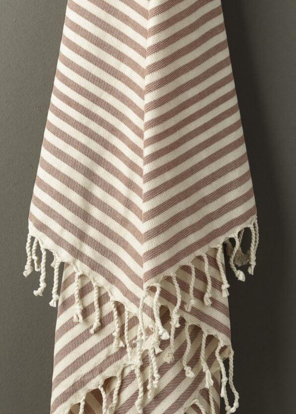 Nært produktbillede af stribet strandhåndklæde i rød