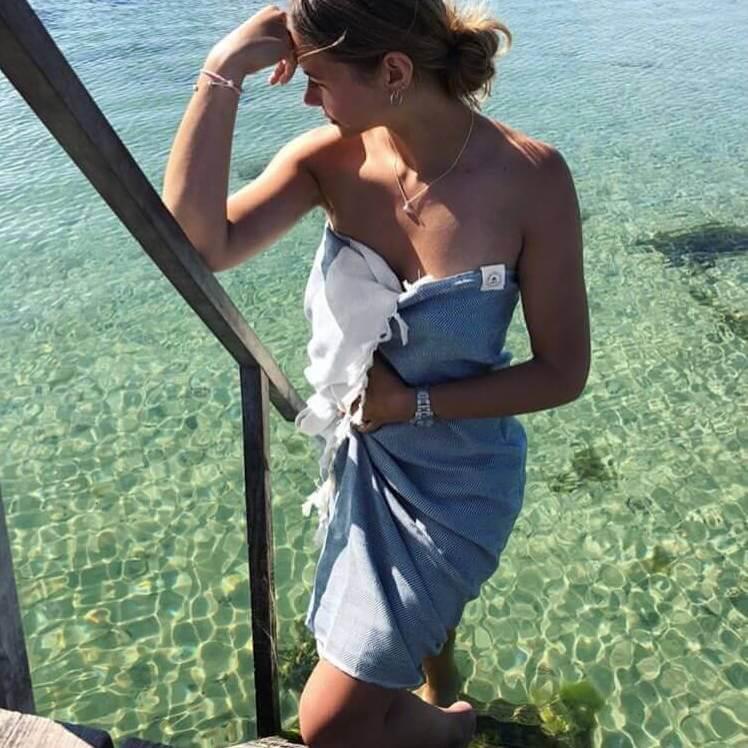 Ung kvinde der tørrer sig i et hurtigtørrende håndklæde
